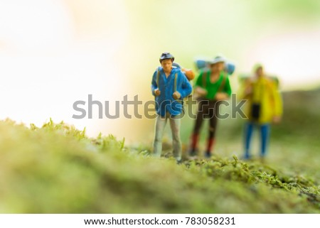 Miniature people : traveler walking on the roads are cluttered with grass. Used to travel to destinations on travel business background concept. #783058231