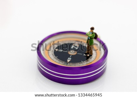 Miniature people: Traveller standing on compass. Travel, explore and adventure concept #1334465945
