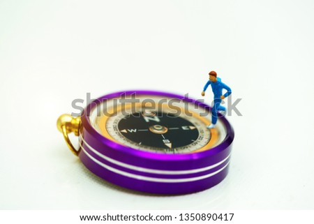 Miniature people: Traveller standing on compass. Travel, explore and adventure concept #1350890417