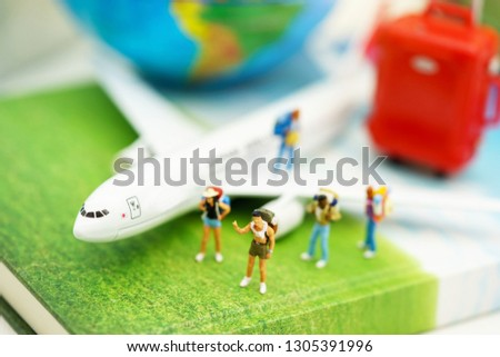 Miniature people: Traveller with backpack walking on the path of tourism by airplane. Travel, explore and adventure concept