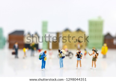 Miniature people: Traveller with backpack walking on the path of tourism. Travel, explore and adventure concept