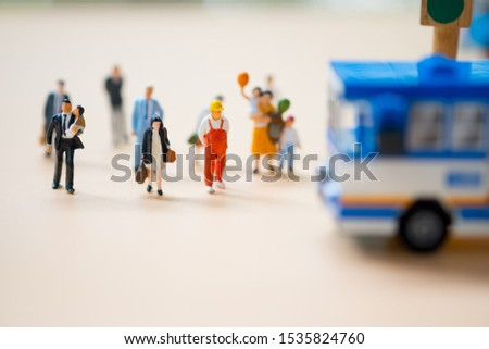 Miniature people wait public public transport at early morning rush hours, busy modern life concept.