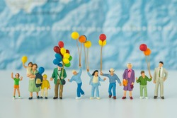 Miniature people with family holding balloons with blue map in the background as happy family or travel concept.