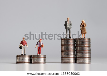 Miniature people with pile of coins. The concept of social stratification according to economic power. Stockfoto ©