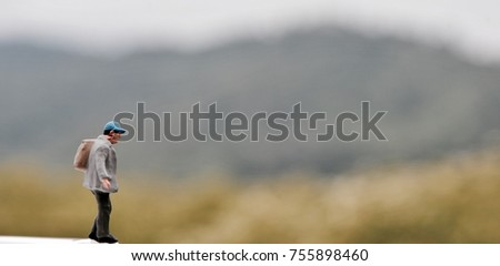 Miniature people with traveling alone concepts, Small hiker figure walking with backback.