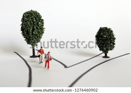 Miniature people with two roads and two trees. The concept of choice and challenge. #1276460902