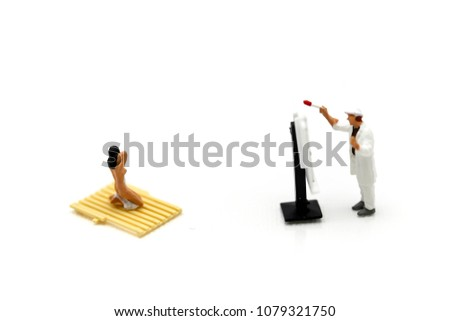 Miniature people , Woman artist painting a picture in a studio ,Nude sexy woman. Perfect naked body of sexy lady.