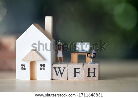 Photo of Miniature people work stand on wood block of WFH. Concept image WFH (WORK FROM HOME). During the Coronavirus crisis. Social Distancing and Physical Distancing. In response to the COVID-19 pandemic.