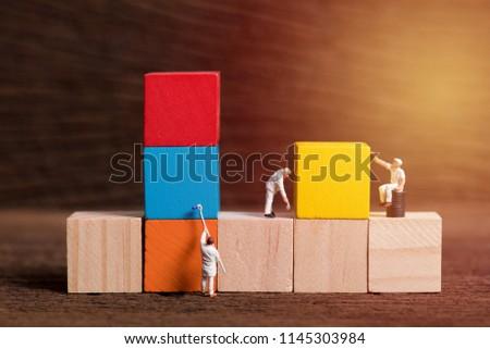 miniature people worker painting wood cube building block , wood background