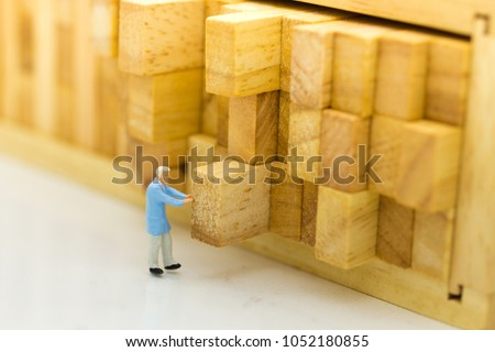 Miniature people : Worker push the wood log back into place. Image use for allocating space to stock, warehouse, business concept.