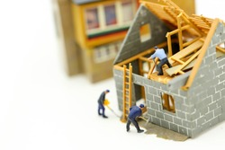 Miniature people : worker team for building home ,Image use for construction, business concept,house repair or home renovating