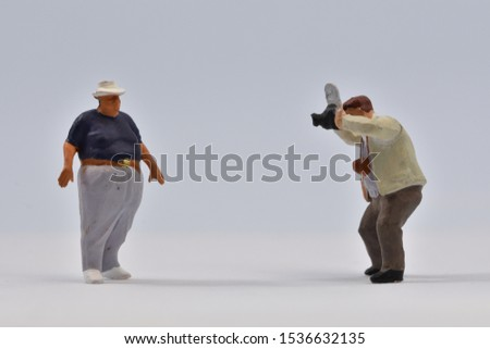 Miniature  photographer is taking a picture of a corpulent guy  with a hat on his head