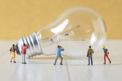miniature photographer take a picture of vintage light bulb