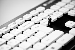 Miniature Police officer on top of computer keyboard. Internet piracy and criminality cpncept.