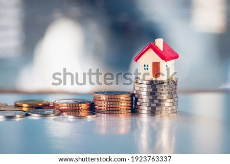 Miniature red house on stack coins using as property real estate and business financial concept