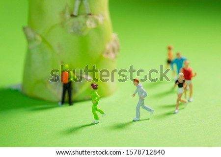 Miniature Runners jogging in a circle around a broccoli to train fitness and endurance for better health