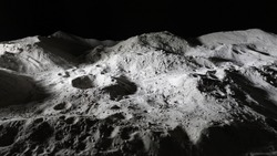Miniature scale model of the Moon surface with its craters, shoot in the studio set under small led lights, with wide angle lens.