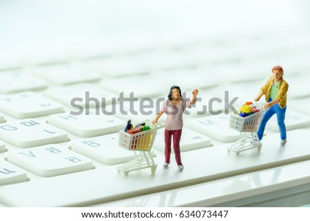 Miniature shoppers push a shopping cart on a keyboard. Concept of decreasing in foot traffic after the coming of online internet ecommerce. E-commerce gives many choices to customers at lower price.