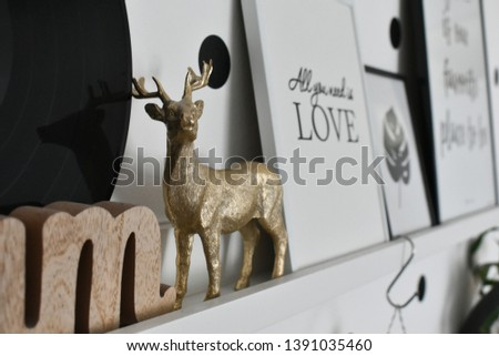 miniature statue of deer in focus on white wooden shelf with isolated pictures behind