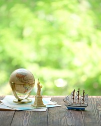 miniature Statue of Liberty, earth globe and ship on wooden table. USA national holiday, Travel world concept. copy space
