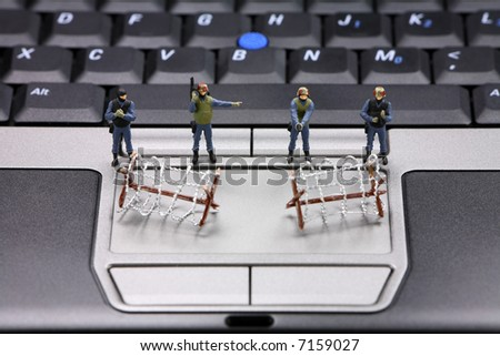 Miniature swat team and barbed wire are guarding a laptop from viruses, spyware and identity thieves. Computer security concept.