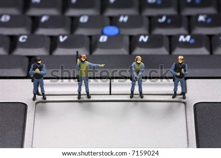 Miniature swat team is guarding a laptop from viruses, spyware and identity thieves. Computer security concept.