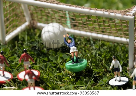 Miniature/table soccer game played on real grass to add more atmosphere. Short depth of field.