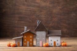 Miniature Thanksgiving Day little cosy fairy tale autumn cottages, pumpkins, wooden background, postcard concept, toned
