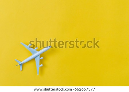 Miniature toy airplane on yellow background. Trip by airplane. stock photo