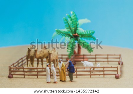 Miniature toy Arab man and wife in abaya buys camel and sheep from a kid on a farm concept. #1455592142