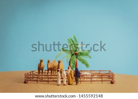 Miniature toy Arab man and wife in abaya buys camel and sheep from a kid on a farm concept. #1455592148