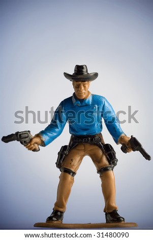miniature toy cowboy drawing both pistols