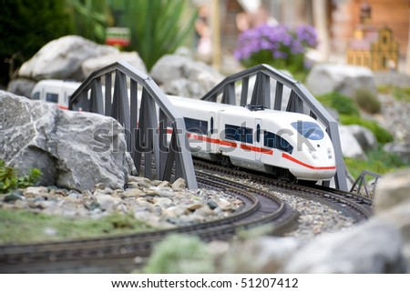 Miniature toy model of modern train crossing bridge