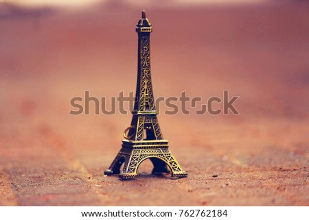 Miniature/Toy of the Eiffel tower on a Brown background. The decoration and the memory of the journey. Part Of Paris. France