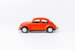 Miniature toy red retro car on white background. Metal model.