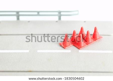 Miniature traffic cone put on the road plate model scene represent road safety concept idea. Photo stock ©