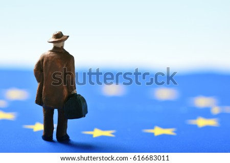 miniature traveler man seen from behind wearing a hat and carrying a suitcase, on an european union flag