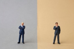 miniature two businessmen stand on opposite sides
