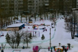 Miniature unrecognizable people in winter. At the playground in kindergarten. Group of walk, play, slide down a children slide, wallow in the snow. Trees, toy houses.