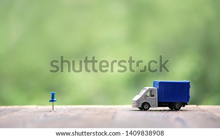 miniature van on wood background. truck toy and destination point indicated by blue pushpin. Concept for visualization of delivery services, logistics, business, forwarding, travel, cargo delivery. #1409838908