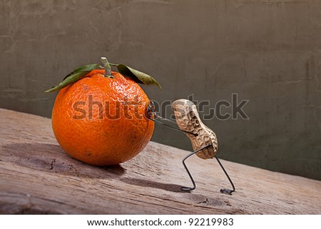 Miniature with Peanut Man pushing heavy orange up the hill, Sisyphos Concept