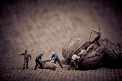 Miniature with workers and walnut. Color tone tuned macro photo
