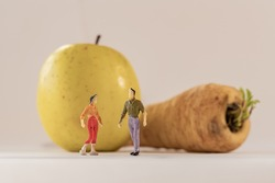 Miniature woman and man figure standing next to big apple and parsnip. Shallow depth of field background. Healthcare, healthy lifestyles and slimming concept.