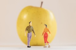 Miniature woman and man figure standing next to big yellow apple. Shallow depth of field background. Healthcare, healthy lifestyles and slimming concept.