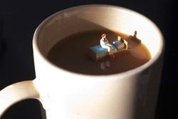 Miniature woman on a bed in a cup of coffee. Waking up with caffeine to start day. Time to start your morning with a hot cup of java. Coffee is a big part of our day.  Insomnia or exhaustion concept.