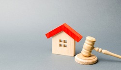 Miniature wooden house and judge's hammer. The concept of resolving property disputes. Property alienation. Confiscated housing. Nationalization. Services of a lawyer. Court. Gavel. Law