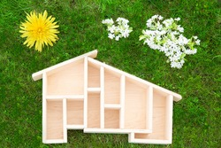 Miniature wooden house on green grass. Floral stylized sun and clouds. Safety. Eco-friendly and energy efficient house. conceptual chimney made of glass and flowers.