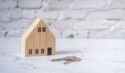 Miniature wooden house with a key on a white brick floor. Insurance, mortgage, trading, home brokerage, housing needs. House prices rising house prices. Eco-friendly housing and falling Copy space