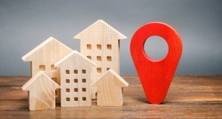 Miniature wooden houses and a geolocation marker. Location of residential buildings. City orientation. Checking the location of a new apartment for infrastructure facilities, parks. Real estate