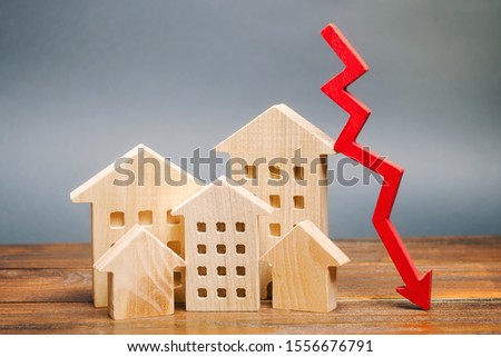 Photo of  Miniature wooden houses and a red arrow down. The concept of low cost real estate. Lower mortgage interest rates. Falling prices for rental housing and apartments. Reducing demand for home buying